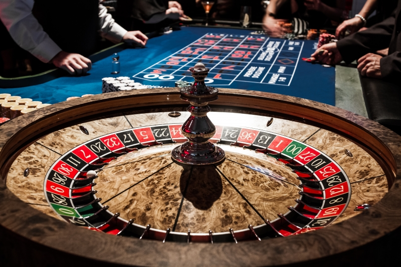8823097-wooden-shiny-roulette-details-in-a-casino-and-people (1)